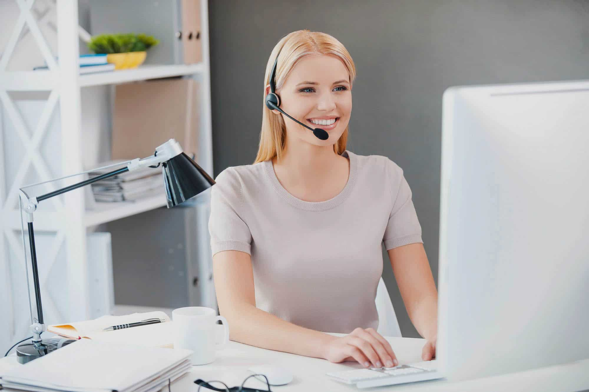 Customer service representative at work. Beautiful young woman in headset working at the computer and smiling while sitting at her working place in office